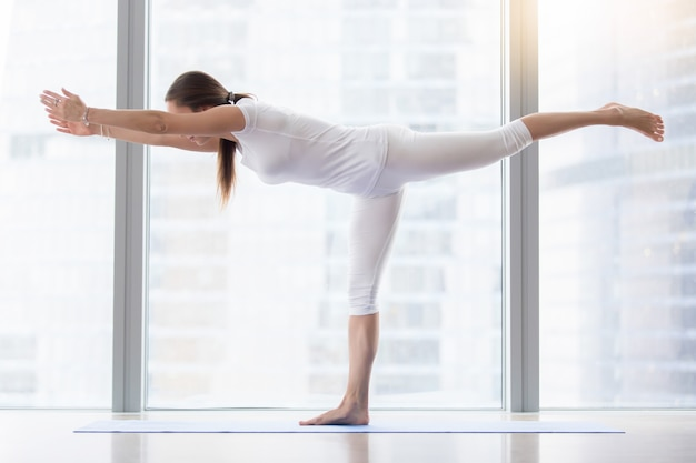 Young attractive woman in virabhadrasana iii pose