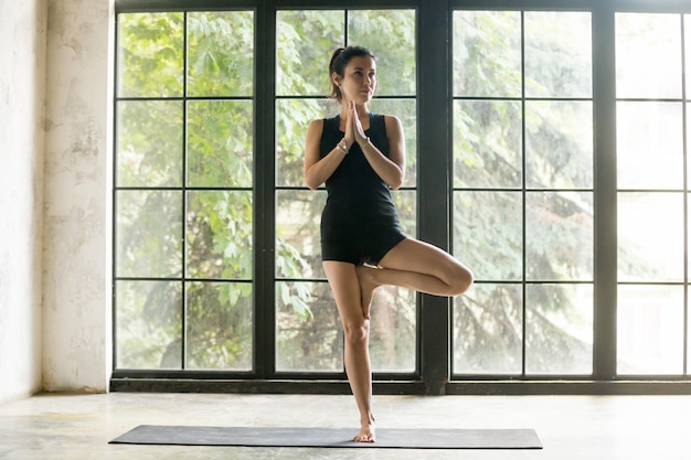 Young attractive woman in vrksasana pose, studio background