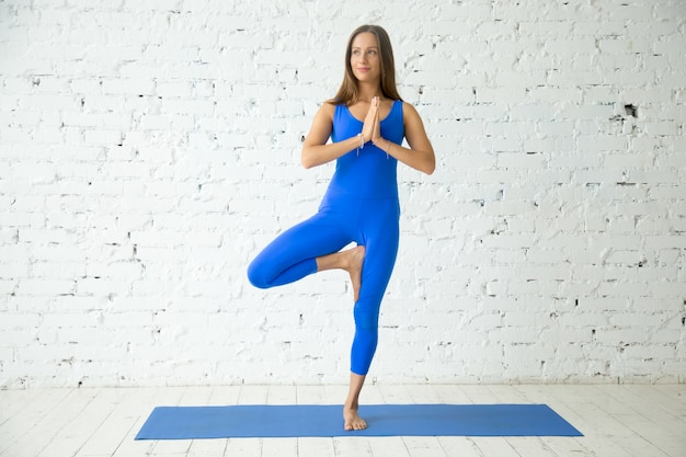 Young attractive woman in vrksasana pose, white studio backgroun