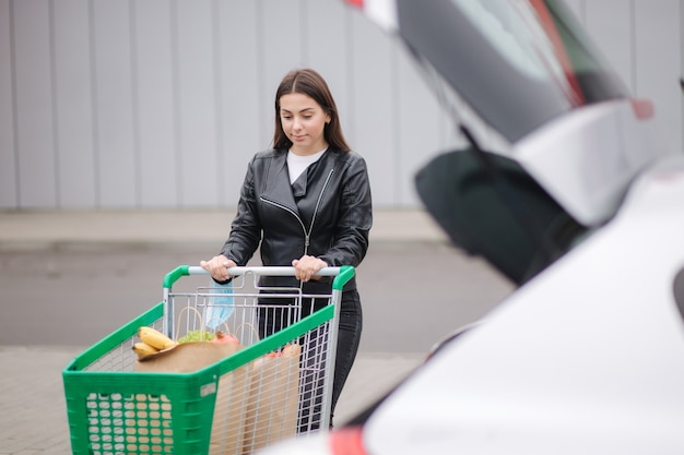 슈퍼마켓에서 트롤리 식료품과 함께 산책하는 젊은 매력적인 여자