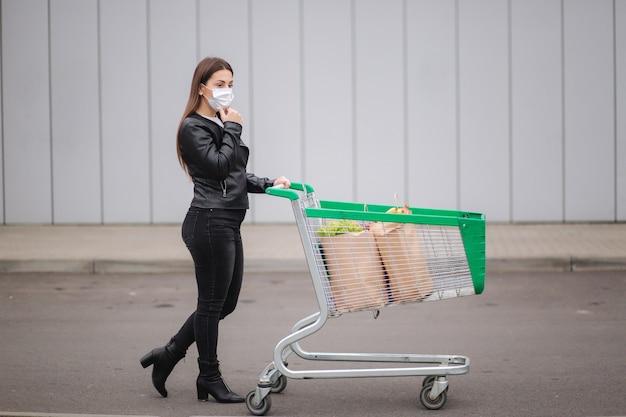 Молодая привлекательная женщина гуляет с продуктами на тележке из супермаркета