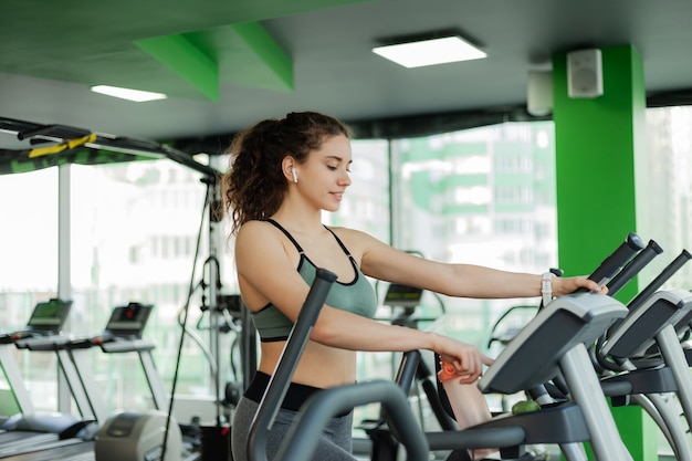 Молодая привлекательная женщина нагревается на эллиптическом тренажере в тренажерном зале. фитнес, концепция здорового образа жизни.