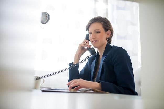파란색 양복을 입은 젊은 여성이 콜센터나 비즈니스 커뮤니케이션의 개념적 대화를 들으며 웃고 있습니다.