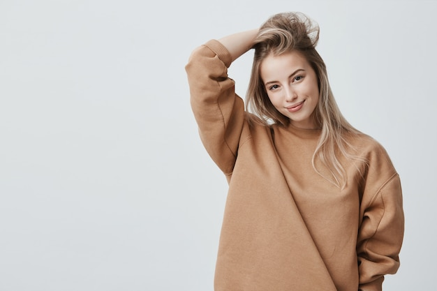 Young attractive woman wearing stylish long-sleeved sweatshirt and posing