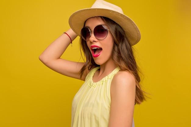Молодая привлекательная женщина носит шляпу и летнее яркое платье позирует