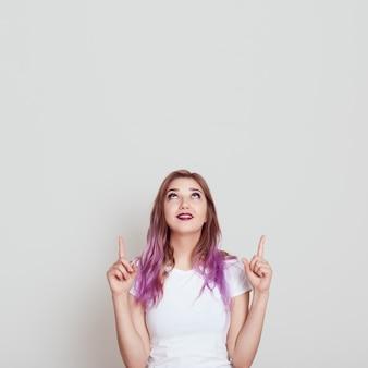 Giovane donna attraente in maglietta casual bianca che osserva e rivolta verso l'alto con entrambi gli indici, copia spazio per pubblicità o testo promozionale, in posa isolato sopra il muro grigio