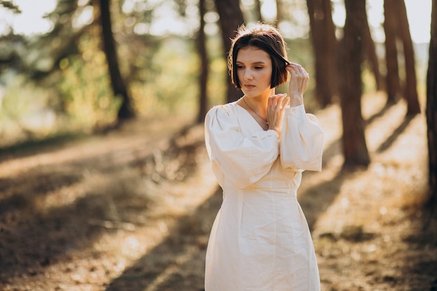 Young attractive woman in white dress in forest