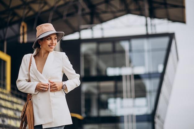 Giovane donna attraente in giacca bianca che cammina all'aperto