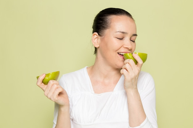 Young attractive woman in white shirt holding and eating sliced green apples