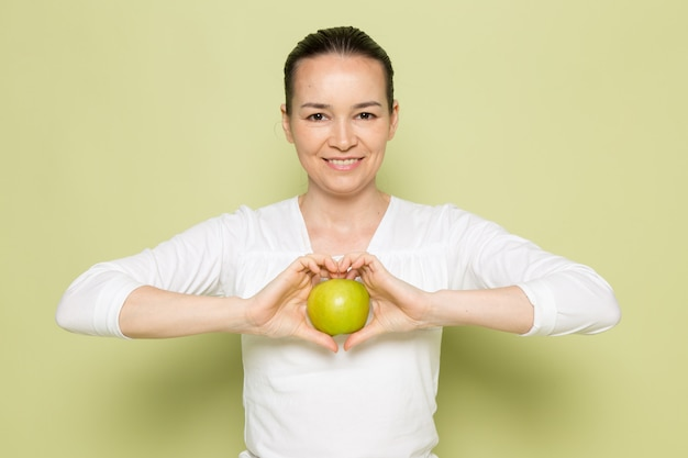 Young attractive woman in white shirt holding green apple