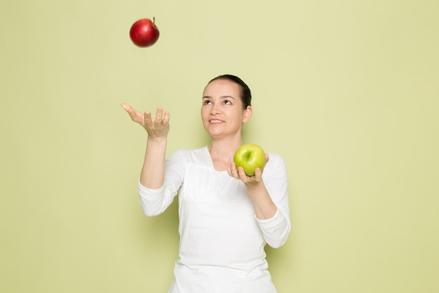 Young attractive woman in white shirt smiling and playing with green and red apples