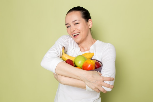 Young attractive woman in white shirt smiling and showing fruit bowl