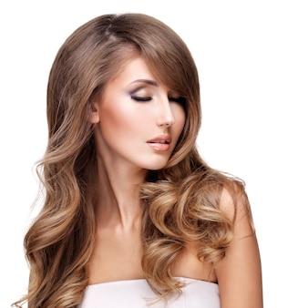 美しい長いウェーブのかかった髪のポーズで若い魅力的な女性。白で隔離