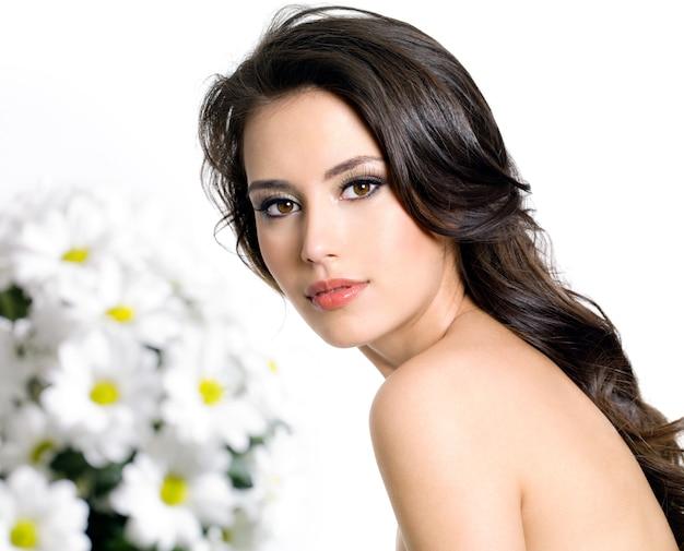 きれいな肌と花の花束を持つ若い魅力的な女性-白で隔離