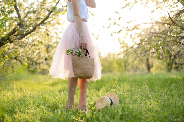 Young attractive woman with curly hair walking in a green flowered garden at sunset. spring romantic mood