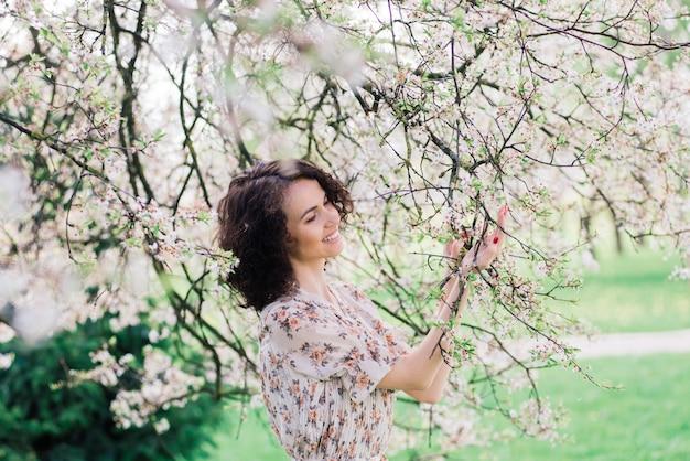 Молодая привлекательная женщина с вьющимися длинными волосами позирует в весеннем цветущем саду, яблони