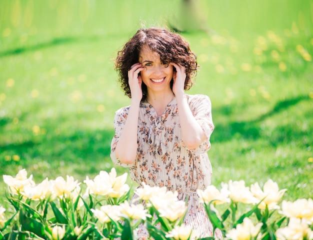 春咲きの庭でポーズをとって巻き毛の長い髪の若い魅力的な女性