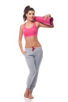 Young attractive woman with exercise mat