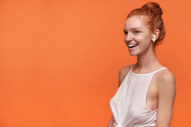 Young attractive woman with foxy bun hairstyle wearing white top and earphones, looking aside with broad cheerful smile, isolated over orange background with hands down