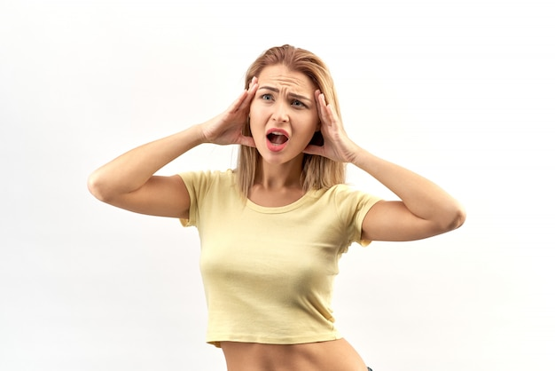 Young attractive woman with hands on head and mouth wide open. shocked, stress, horror emotions on her face and a headache