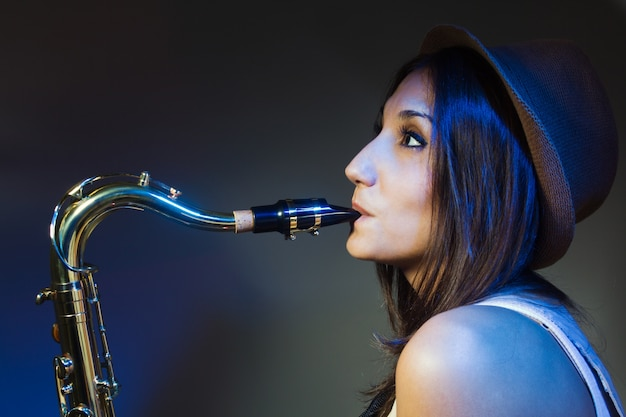 Young and attractive woman with hat playing the saxophone