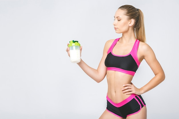 Young attractive woman with healthy diet protein shake drinking for sport and fitness
