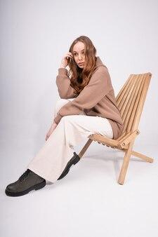 Молодая привлекательная женщина с длинными волосами в пастельной повседневной одежде, сидя на стуле. кавказская девушка позирует