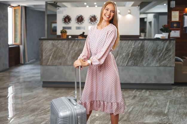 Молодая привлекательная женщина с упакованным чемоданом, стоящая в холле отеля