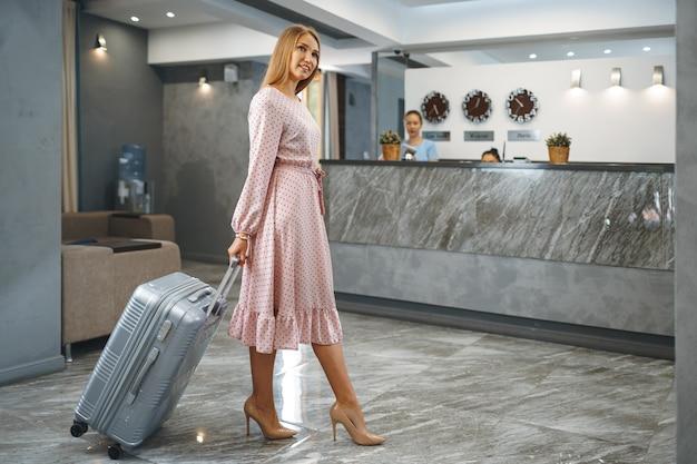 ホテルのロビーに立っているパックされたスーツケースを持つ若い魅力的な女性