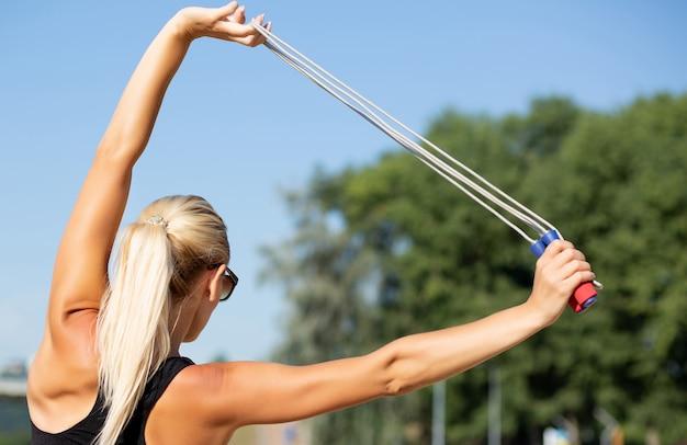 縄跳びでストレッチをする完璧なスリムな体を持つ若い魅力的な女性。クローズアップショット