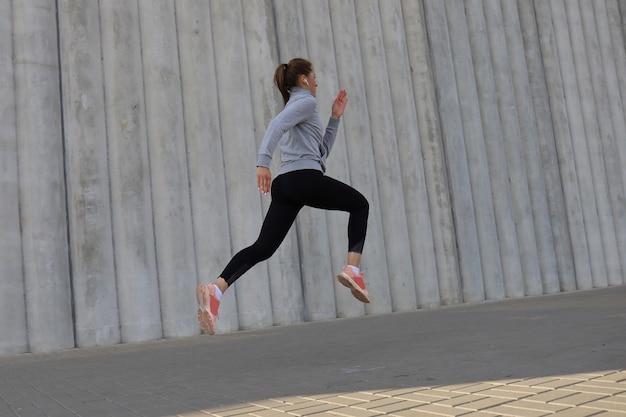 屋外で走る完璧なスリムな体を持つ若い魅力的な女性。フィットネスとランニングのコンセプト。