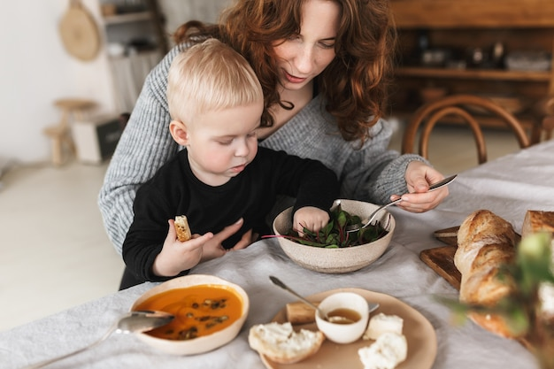 Young attractive woman with red hair in knitted sweater sitting at the table feeding her little son