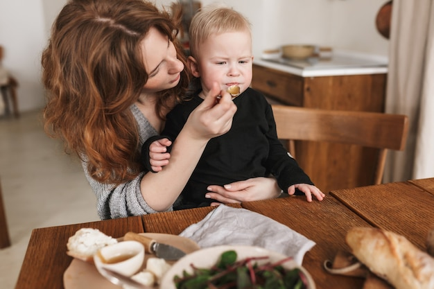 Young attractive woman with red hair in knitted sweater sitting at the table with food thoughtfully feeding her little son