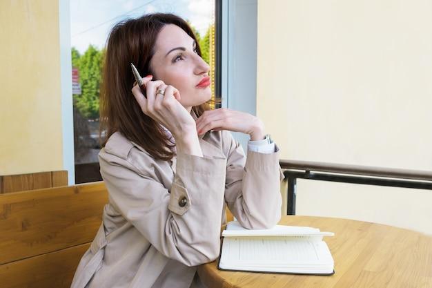 Молодая привлекательная женщина с рыжими волосами сидит на улице за столиком в кафе с бумажным блокнотом и ручкой и задумчиво смотрит вдаль. женщина составляет список дел. blogger составляет контент-план.