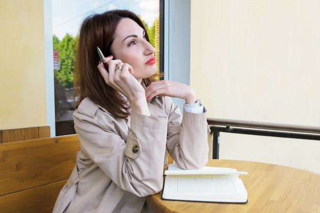 Young attractive woman with red hair sits on the street at a cafe table with paper notebook and pen and looks thoughtfully into the distance. woman makes a to-do list. blogger makes a content plan.