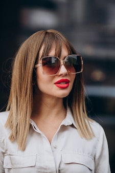 通りでポーズをとって赤い唇を持つ若い魅力的な女性