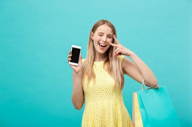 買い物袋を持つ若い魅力的な女性は、カメラの電話の画面を直接示しています。