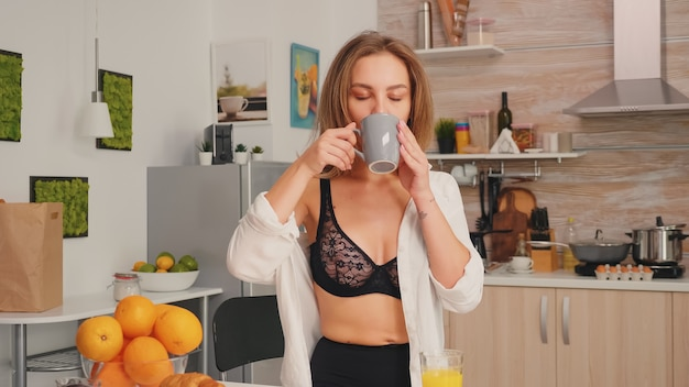 Young attractive woman with tattoos in seductive underwear holding cup of tea relaxing in the kitchen smiling. sexy blonde lady in lingerie drinking coffee during breakfast enjoying the morning.