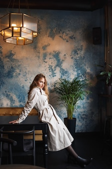 Young attractive woman with wavy hair in striped trench coat leaning on table dreamily