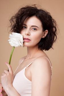 Молодая привлекательная женщина с белым цветком возле лица