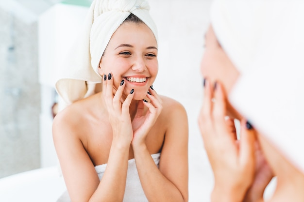 Young attractive woman with white towel on head and body with reflection in mirror in bathroom.