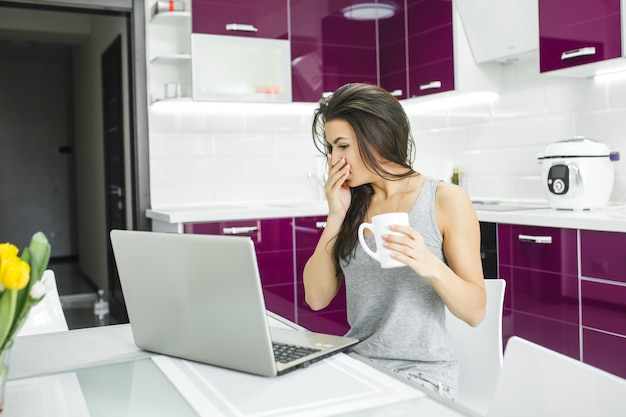 Молодая привлекательная женщина работает на пк на кухне. женщина работает на компьютере в первой половине дня. фрилансер за ноутбуком в помещении.