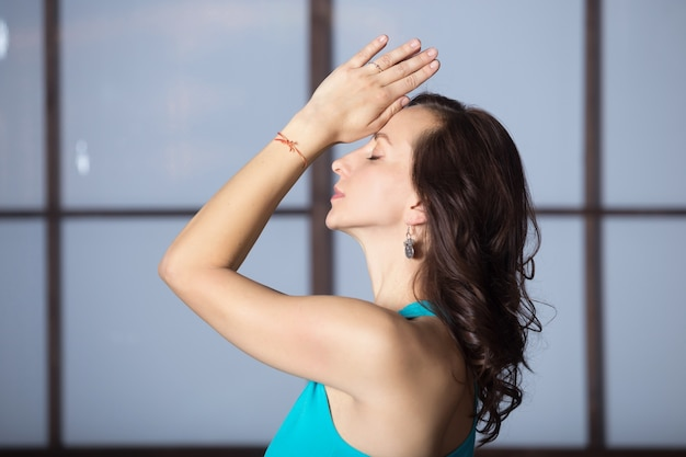 Young attractive woman in yoga pose, studio evening practice