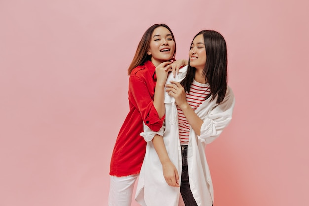 Le giovani donne attraenti si divertono sul muro rosa isolato
