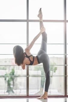La giovane donna attraente yoga che pratica l'allenamento è in abbigliamento sportivo.