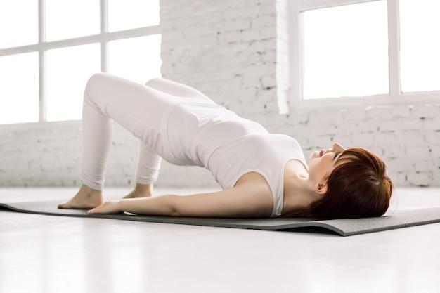 Концепция йоги молодой привлекательной женщины йога практикуя, делая тренировку моста клейковины