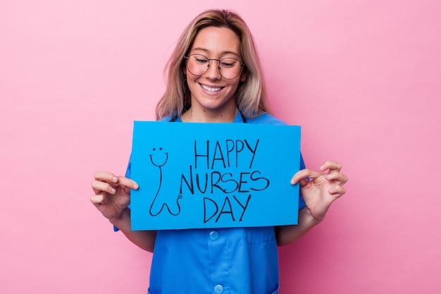 青い背景で隔離の国際看護師の日プラカードを保持している若いオーストラリアの看護師の女性