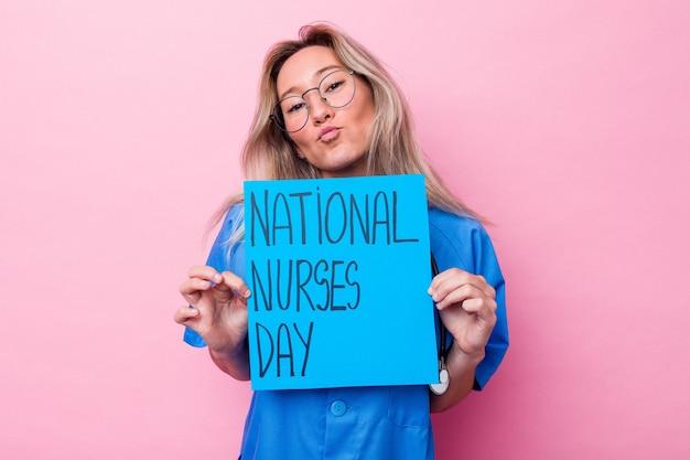 青の背景に分離された国際看護師の日のプラカードを保持している若いオーストラリア人看護師女性