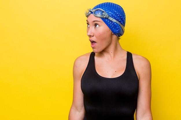 Молодая австралийская женщина-пловец изолирована на желтом фоне, шокирована из-за чего-то, что она видела.