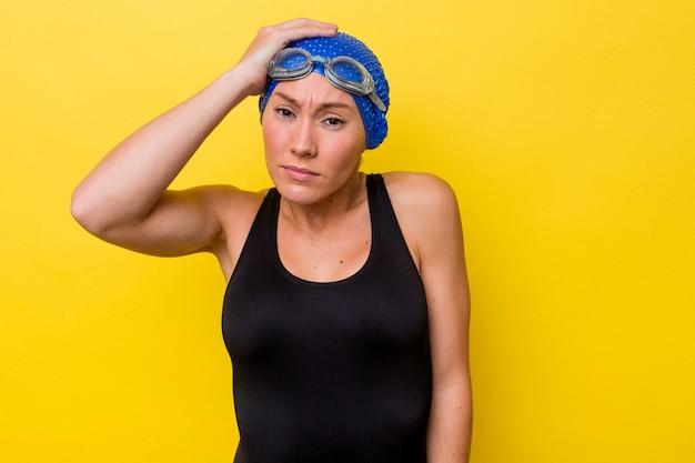 ショックを受けている黄色の背景に孤立した若いオーストラリアの水泳選手の女性、彼女は重要な会議を覚えています。